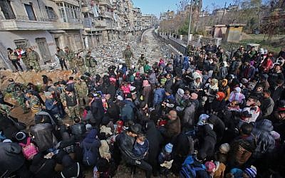 Syrian residents fleeing the violence gather at a checkpoint, manned by pro-government forces, in the Maysaloun neighborhood of the northern embattled Syrian city of Aleppo on December 8, 2016. (AFP/Youssef Karwashan)