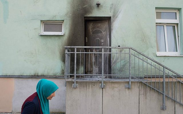 Illustrative image of a woman with a headscarf walking past the entrance to the Fatih Camii Mosque in Dresden, eastern Germany, where traces of smoke can be seen after a bomb attack, September 27, 2016. (Sebastian Kahnert/dpa/AFP)