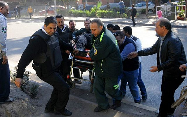 Egyptian emergency services carry a wounded victim at the site of a bomb attack next to a police checkpoint in the western Talibiya district of the capital Cairo on December 9, 2016. (Stringer/AFP)