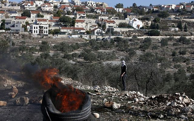 A Palestinian protester looks at burning tires during clashes with Israeli security forces near the settlement of Kedumim in the West Bank on December 9, 2016. (AFP/JAAFAR ASHTIYEH)