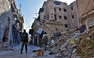 Syrian pro-government forces walks past rubble in old Aleppo's Jdeideh neighborhood on December 9, 2016. (AFP/George Ourfalian)