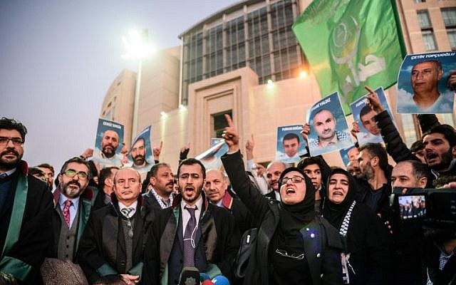 Lawyers and families hold pictures of victims and shout slogans on December 9, 2016 outside the Istanbul courthouse as Turkish court is expected to rule in the case of Israelis charged in absentia over a deadly commando raid on a Gaza-bound aid ship in 2010. (AFP/OZAN KOSE)