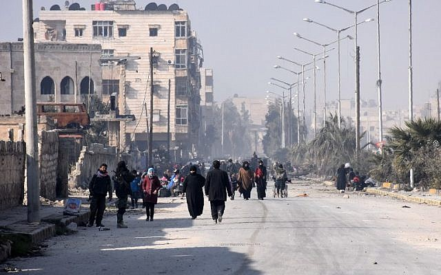 Syrian civilians walk towards a checkpoint manned by pro-government forces, at the al-Hawoz street roundabout, after leaving Aleppo's eastern neighborhoods on December 10, 2016. (AFP PHOTO / George OURFALIAN)