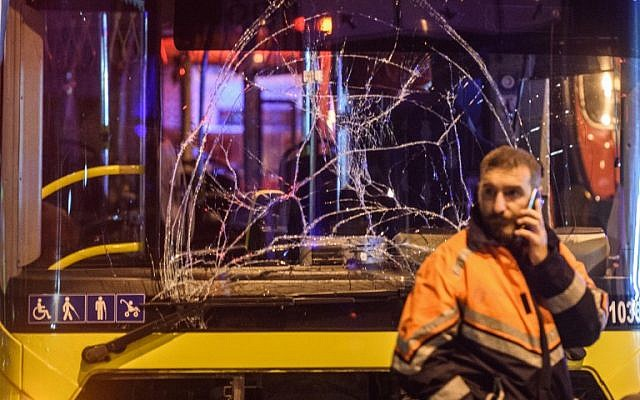 A Turkish emergency worker stand in front of a damaged bus on the site where a car bomb exploded near the stadium of football club Besiktas in central Istanbul on December 10, 2016. (AFP PHOTO / OZAN KOSE)