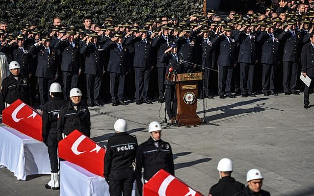 A day after twin bombings, Turkish police officers salute the coffins of their comrades during a funeral ceremony at Istanbul's police headquarters, December 11, 2016. (AFP/OZAN KOSE)