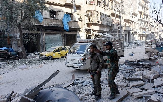 Syrian pro-government forces stand on a street in al-Maadi district of eastern Aleppo on December 11, 2016 after they retook a large part of it from rebel fighters. (AFP/George OURFALIAN)