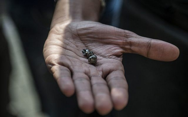 An Egyptian man shows small pieces of metal outside the Saint Peter and Saint Paul Coptic Orthodox Church after it was targeted by a bomb explosion on December 11, 2016, in Cairo's Abbasiya neighborhood. (AFP PHOTO / KHALED DESOUKI)