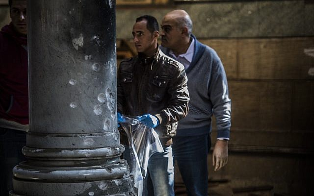 Egyptian security forces inspect the scene of a bomb explosion at the Saint Peter and Saint Paul Coptic Orthodox Church on December 11, 2016, in Cairo's Abbasiya neighborhood. (AFP PHOTO / KHALED DESOUKI)