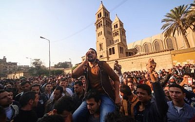 Egyptians shout slogans as they gather outside the the Saint Peter and Saint Paul Coptic Orthodox Church in Cairo's Abbasiya neighbourhood after it was targeted by a bomb explosion on December 11, 2016, (AFP PHOTO / MOHAMED METEAB)