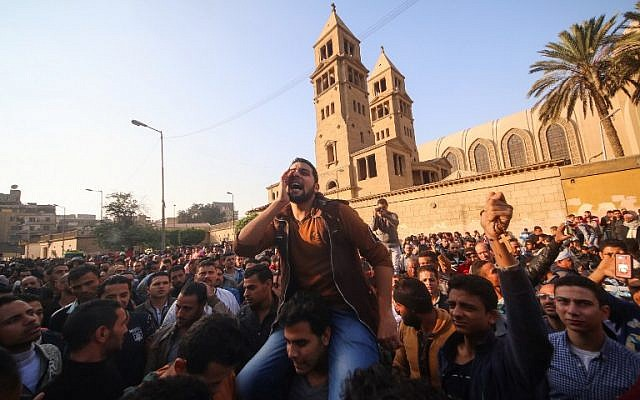 Egyptians shout slogans as they gather outside the the Saint Peter and Saint Paul Coptic Orthodox Church in Cairo's Abbasiya neighborhood after it was targeted by a bomb explosion on December 11, 2016, (AFP PHOTO / MOHAMED METEAB)