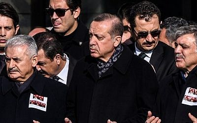 Turkish President Recep Tayyip Erdogan, center, Prime Minister Binali Yildirim, left, and former president Abdullah Gul, right, pray at a funeral ceremony for police officers killed at Istanbul's police headquarters on December 11, 2016. (AFP Photo/Ozan Kose)