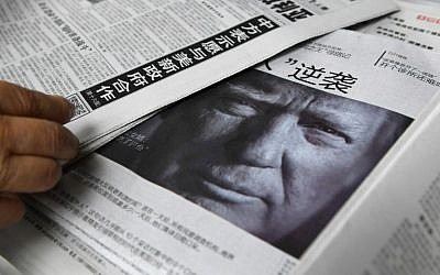 This photo taken on November 10, 2016, shows a newspaper featuring a photo of US President-elect Donald Trump at a newsstand in Beijing.  (AFP/Greg Baker)