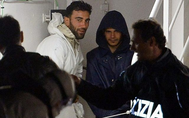 This photo taken on April 20, 2015 shows two men, identified as Mohammed Ali Malek (2nd L), one of the survivors and understood to be the captain of the boat that overturned off the coasts of Libya, and a man identified as Mahmud Bikhit (2nd R), another survivor and understood to be a crew member of the boat, standing onboard the Italian Coast Guard vessel Bruno Gregoretti at Boiler Wharf, Senglea, in Malta. (AFP PHOTO / ALBERTO PIZZOLI)