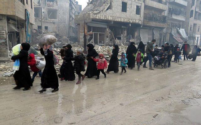 Syrian residents, fleeing violence in the restive Bustan al-Qasr neighbourhood, arrive in Aleppo's Fardos neighborhood on December 13, 2016, after regime troops retook the area from rebel fighters. (AFP/STRINGER)
