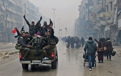 Syrian pro-regime fighters gesture as they drive past residents fleeing violence in the restive Bustan al-Qasr neighborhood, in Aleppo. December 13, 2016. (AFP/Stringer)