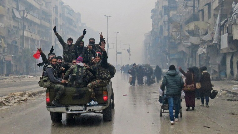 Syrian pro-regime fighters gesture as they drive past residents fleeing violence in the restive Bustan al-Qasr neighborhood, in Aleppo. December 13, 2016. (AFP PHOTO/STRINGER)