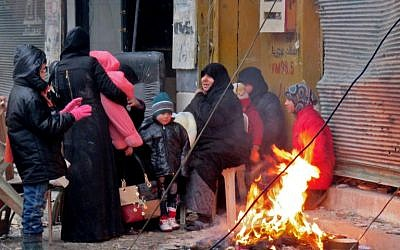 Syrians keep warm next to a fire in Aleppo's Fardos neighborhood, after fleeing violence in the restive Bustan al-Qasr neighborhood, on December 13, 2016. (AFP PHOTO/STRINGER)