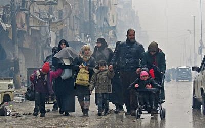 Syrian residents, fleeing violence in the restive Bustan al-Qasr neighborhood, arrive in Aleppo's Fardos neighborhood on December 13, 2016, after regime troops retook the area from rebel fighters. (AFP PHOTO / STRINGER)