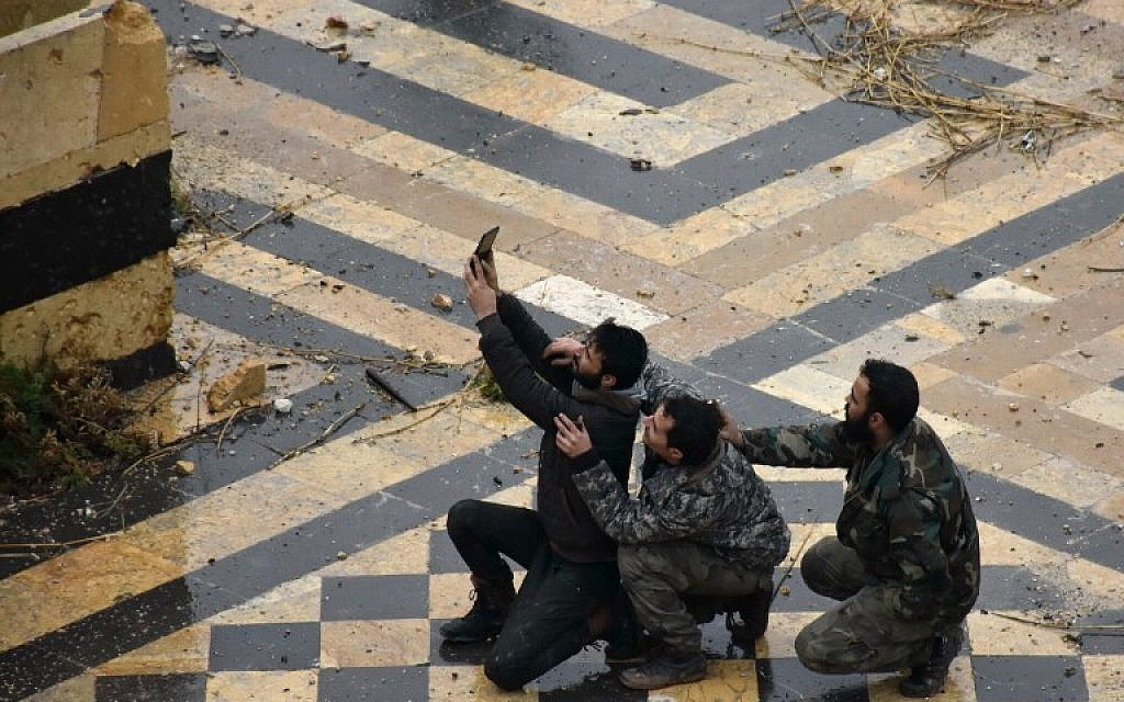 Syrian pro-government forces take a selfie in the courtyard of the ancient Umayyad mosque in the old city of Aleppo on December 13, 2016. (AFP PHOTO/George OURFALIAN)