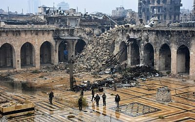 Syrian pro-government forces walking in the ancient Umayyad mosque in the old city of Aleppo on December 13, 2016, after they captured the area. ( AFP PHOTO / George OURFALIAN)