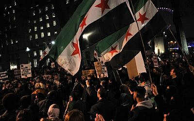 Protesters wave flags during a demonstration in solidarity with the inhabitants of the embattled Syrian city of Aleppo, outside the entrance to Downing Street, in central London on December 13, 2016.(AFP PHOTO / Daniel SORABJI