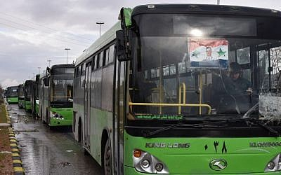 Buses which are expected to be used to evacuate civilians leaving from rebel-held areas of Aleppo are seen waiting on December 14, 2016. (AFP Photo/George Ourfalian)