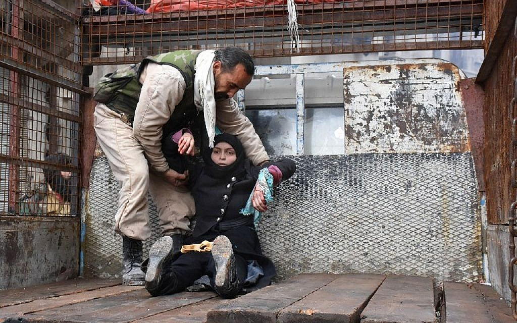 A wounded Syrian woman from the al-Sukari neighborhood is helped onto the back of a truck as she flees during the ongoing government operation to retake remaining rebel-held areas in Aleppo on December 14, 2016. (AFP PHOTO/George OURFALIAN)