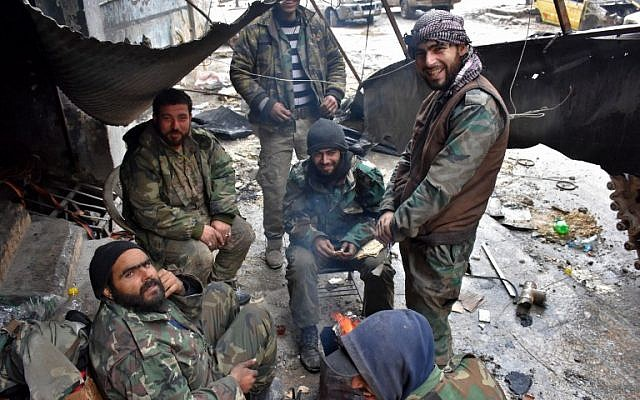Syrian pro-government forces take a break as they advance in the Jisr al-Haj neighborhood during the ongoing military operation to retake remaining rebel-held areas in the northern embattled city of Aleppo on December 14, 2016. (AFP PHOTO / George OURFALIAN)