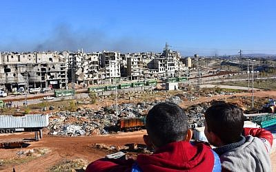 Syrian children watch on as buses depart during an evacuation operation of rebel fighters and their families from rebel-held neighborhoods in the embattled city of Aleppo on December 15, 2016 (AFP PHOTO / George OURFALIAN)