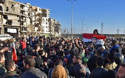 A man holds a Syrian flag bearing the portrait of President Bashar Assad as residents in a government-held area of Aleppo gather in the street during an evacuation of rebel fighters and their families on December 15, 2016. (AFP/George Ourfalian)