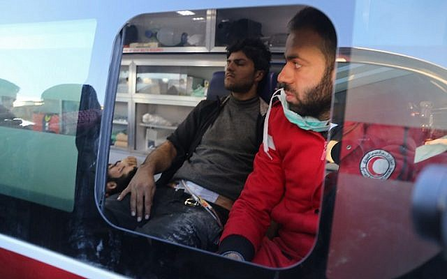Wounded Syrian men, evacuated from rebel-held neighborhoods of Aleppo, sit in a Syrian Arab Red Crescent ambulance upon their arrival in the opposition-controlled Khan al-Aassal region, west of the city, on December 15, 2016. (AFP PHOTO/Baraa Al-Halabi)