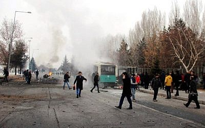 This picture obtained from the Ihlas News Agency shows a police officer and people walking next to the wreck of public bus following an explosion on December 17, 2016 in Kayseri, central Turkey. (AFP PHOTO / IHLAS NEWS AGENCY / IHLAS NEWS AGENCY)
