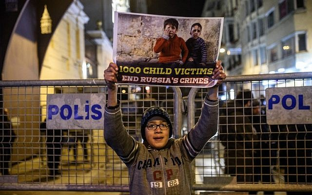 A Syrian boy living in Turkey holds a sign during a protest against Russia, Syrian president Bashar al-Assad's regime ally, in front of the Russian Embassy along Istiklal Avenue in Istanbul on December 17, 2016. (AFP PHOTO/OZAN KOSE)