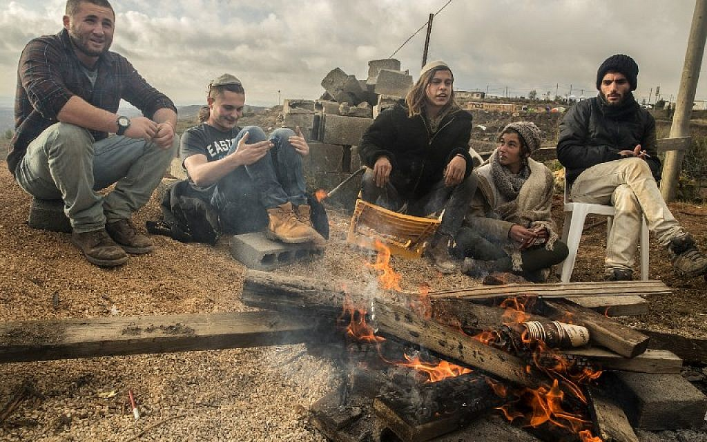 Young Israeli settlers gather around a fire in the settlement outpost of Amona on December 18, 2016. (AFP/JACK GUEZ)