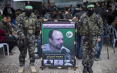 Members of the Izz ad-Din al-Qassam Brigades, the military wing of Hamas, hold a banner bearing a portrait of one of their top scientists, Mohamed Zoari, who was killed in Tunisia on December 15, 2018, during a ceremony in his memory on December 18, 2016, in Gaza City. (AFP Photo/Mahmud Hams)