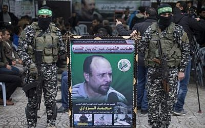 Members of the Izz ad-Din al-Qassam Brigades, the military wing of Hamas, hold a banner bearing a portrait of Mohammed al-Zoari in Gaza City on December 18, 2016. (AFP/Mahmud Hams)