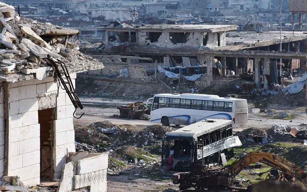 A bus drives through the government-controlled crossing of Ramoussa, on the southern outskirts of Aleppo, on December 18, 2016, during an evacuation operation of rebel fighters and civilians from rebel-held areas. (AFP/George OURFALIAN)