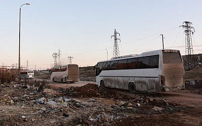 Buses drive through the Syrian government-controlled crossing of Ramoussa, on the southern outskirts of Aleppo, on December 18, 2016, during an evacuation operation of rebel fighters and civilians from rebel-held areas. (AFP PHOTO / George OURFALIAN)
