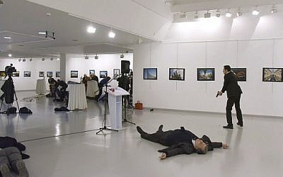 This picture taken on December 19, 2016 shows Andrei Karlov (2ndR), the Russian ambassador to Ankara, lying on the floor after being shot by Mevlut Mert Altintas (R) during an attack during a public event in Ankara. (AFP PHOTO / Sozcu daily / Yavuz Alatan)