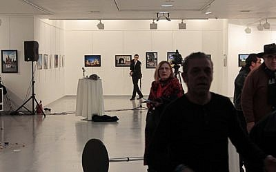This picture taken on December 19, 2016 in Ankara shows guests leaving a gallery as a gunman holds a weapon, during an attack where Andrey Karlov, the Russian ambassador to Ankara, was shot. (AFP/ Hurryet/Hasim KILIC)