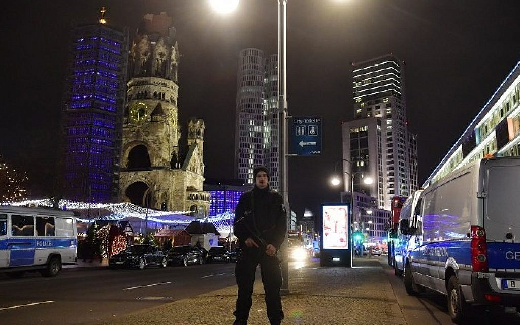 A police man stands at the site where a truck speeded into a Christmas market in Berlin, on December 19, 2016 killing nine persons and injuring at least 50 people. (AFP PHOTO / John MACDOUGALL)