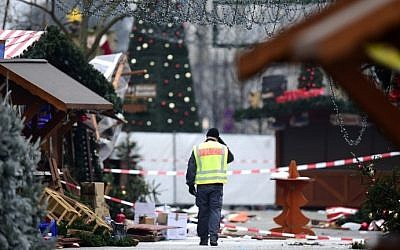 A policeman walks at the Christmas market near the Kaiser Wilhelm Memorial Church, the day after a terror attack, in central Berlin, on December 20, 2016. (AFP Photo/Tobias Schwarz)