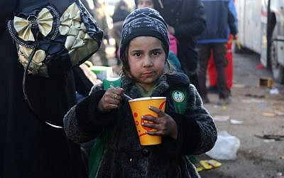 A Syrian girl, who was evacuated from the last rebel-held pockets of Syria's northen city of Aleppo, eats upon arriving on December 20, 2016 in the opposition-controlled Khan al-Assal region, west of the embattled city. (AFP PHOTO / Baraa Al-Halabi)