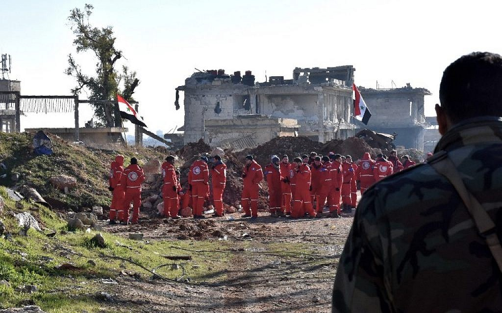 Syrian government forces and Red Crescent staff are seen in Aleppo's Ramoussa district as the evacuation of civilians from eastern Aleppo continues on December 20, 2016. (AFP PHOTO / GEORGE OURFALIAN)