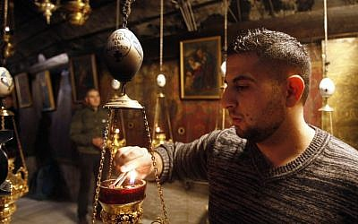 A man lights incense at the Church of the Nativity, believed to be the birthplace of Jesus Christ, in the West Bank city of Bethlehem on December 20, 2016. (AFP PHOTO / MUSA AL SHAER)