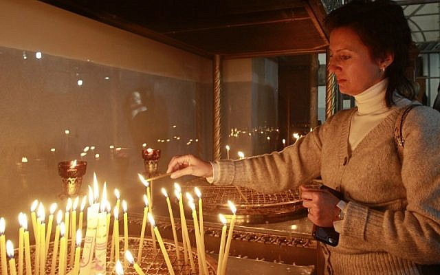 A Christian woman lights a candle at the Church of the Nativity, believed to be the birthplace of Jesus Christ, in the West Bank city of Bethlehem on December 20, 2016. (AFP PHOTO / MUSA AL SHAER)