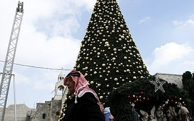 A Palestinian man walks past a Christmas tree at the Manger Square near the Church of the Nativity, on December 20, 2016 in the biblical town of Bethlehem in the West Bank. (AFP / MUSA AL SHAER)