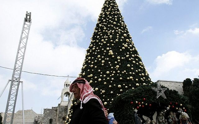A Palestinian man walks past a Christmas tree at the Manger Square near the Church of the Nativity, revered as the site of Jesus' birth, on December 20, 2016, in the West Bank town of Bethlehem. (AFP PHOTO / MUSA AL SHAER)