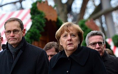 German Chancellor Angela Merkel (C), Berlin Mayor Michael Mueller (L) and German Interior Minister Thomas de Maiziere (R) visit the site of a terror attack at a Christmas market in Berlin on December 20, 2016. (AFP PHOTO/DPA/Maurizio Gambarini)