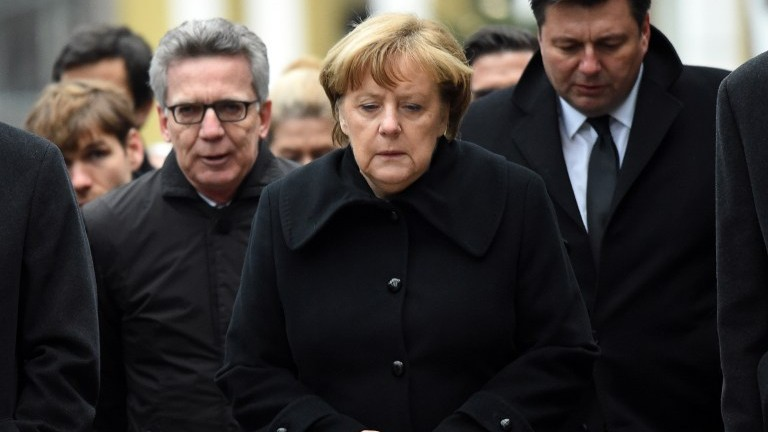 German Chancellor Angela Merkel (C) and German Interior Minister Thomas de Maiziere (L) arrive on December 20, 2016 at the site where a truck crashed into a Christmas market near the Kaiser Wilhelm Memorial Church in Berlin. (AFP Photo/DPA/Maurizio Gambarini)